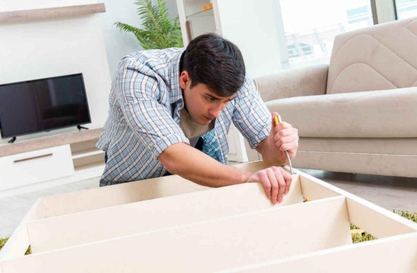 Homme qui monte un meuble